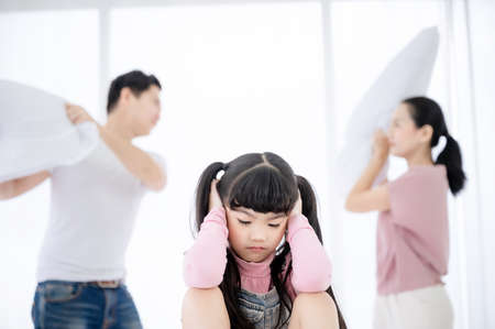 Asian daughter sad and closing her ears while parent quarrelling and fighting in bedroom 免版税图像