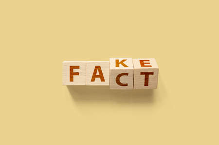 Fact or Fake concept. Wooden cube shape flip change the word. April fools day Фото со стока