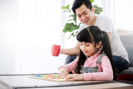 Asian daughter with parent playing toy puzzle on table at home. Kid girl is smiling and enjoy activity leisure