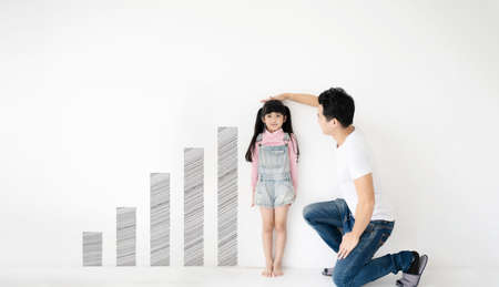 Dad measures height increase of her child daughter at white brick wall with graph growing growth