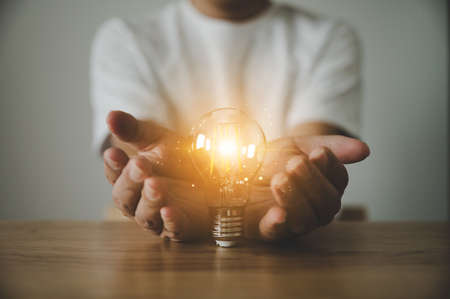 Hand holding light bulb on wood table. Concept of inspiration creative idea thinking and future technology innovation
