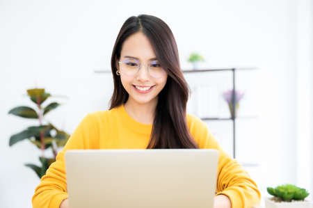 Young asian woman using laptop at house. Work at home, Video conference, Online meeting video call, Virtual meetings, Remote learning, E-learning and Online Education 免版税图像