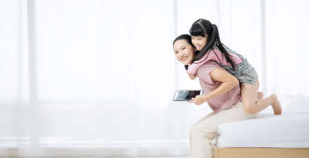 Happy loving asian family. Mother and her daughter child girl playing and hugging on bed in bedroom