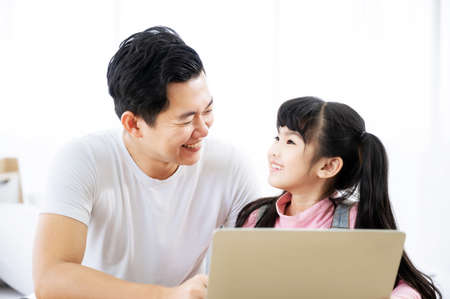 Father and daughter learning education study online class. Kid girl and dad using computer laptop at home