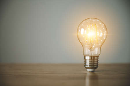 Light bulb on wood table with copy space. Concept of inspiration creative idea thinking and future technology innovation