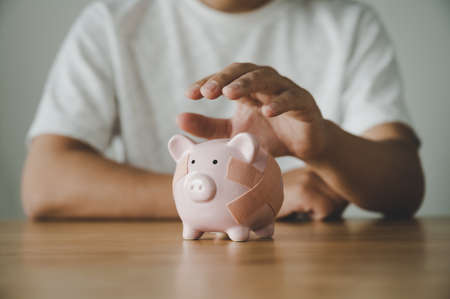 Man hand holding piggy bank on wooden table. Concept of save money and finance business investment Foto de archivo
