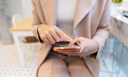 Hand of businesswoman using mobile smart phone at cafe