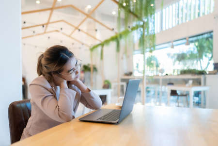 Office syndrome concept. Young asian businesswoman feeling pain in neck after working on computer laptop for a long time in a coffee shop cafe