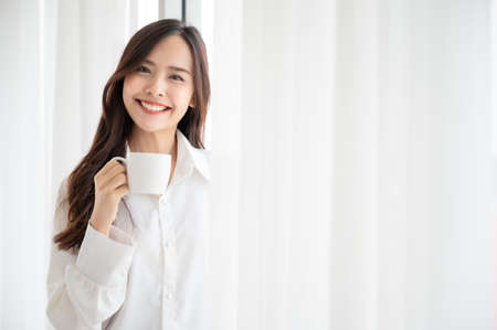 Young asian beautiful woman clothing white pyjamas and drink coffee beside window at morning in bedroom. She feeling happy fresh and smile relax