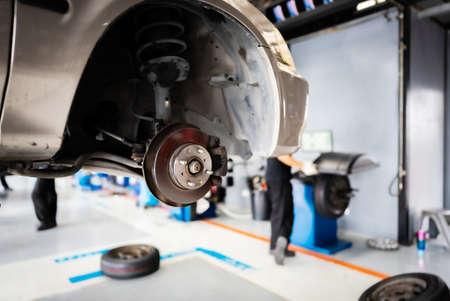 Car repairing or changing wheel in auto repair shop