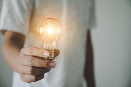 Hand of man holding light bulb. Concept of inspiration creative idea thinking and future technology innovation 版權商用圖片