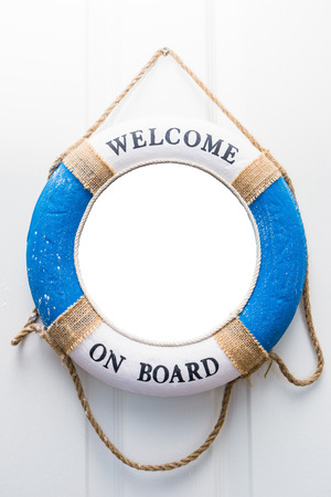 Life buoy mirror isolate with welcome on board on white wood door
