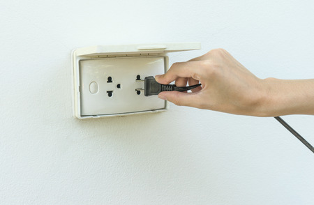 unplugging: Female hand plugging in appliance to electrical outlet in wall