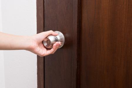 woman handle success: hand hold handle of wood door