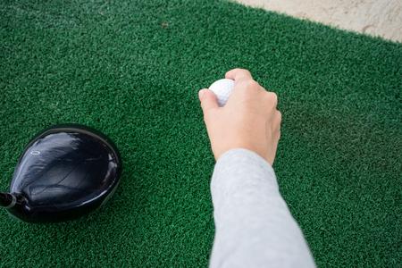 Close-up main tenant une balle de golf et un bois de golf sur un practice