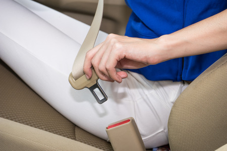 woman hand fastening a seat belt in the car Stock Photo