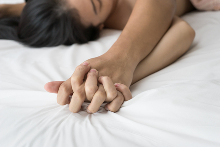 man and woman sex: Young couple making love in bed focus on hand