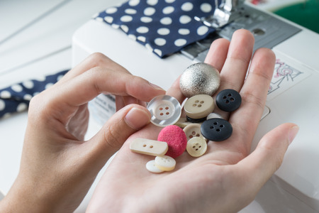 stitchwork: Choose buttons in woman hands , close up Stock Photo