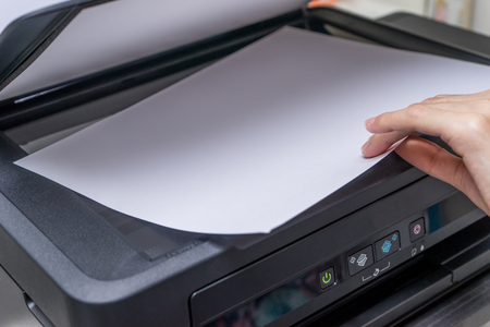 Close up Womans hand with working copier, printer Stock Photo