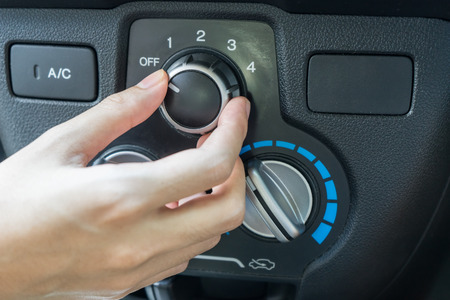 conditions: Woman hand turning on car air conditioning system