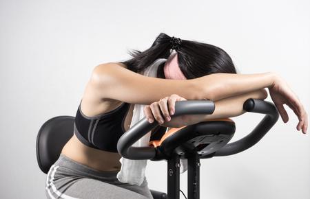 Woman sleep on exercise bike over white background Stock Photo