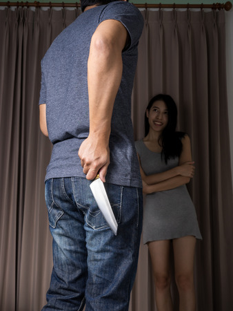 completely: Man holding behind the back knife and talk with woman Stock Photo