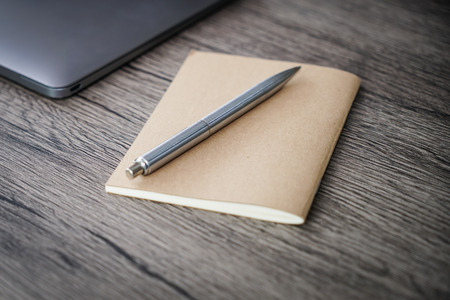 Notebook and pen on wood table