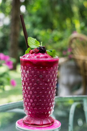 the glass of berry juice smoothie in garden