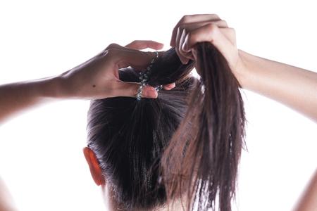 Asian woman tying her hair Stock Photo
