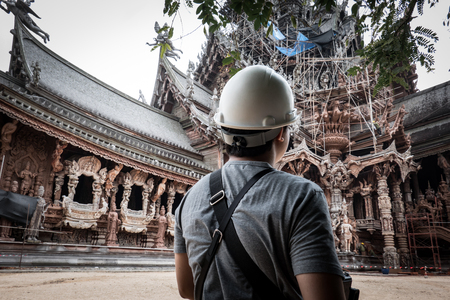 Back of engineer wearing a white helmet looking to construction building wood temple