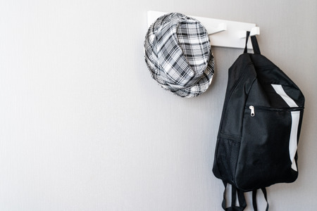 black and white Backpack and scott hat Hanging On white Wall