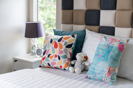 modern bedroom with many pillows on bed Stock Photo