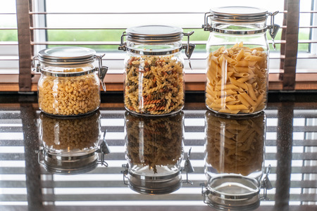 Pasta Fusilli and macaroni in glass bottle in kitchen