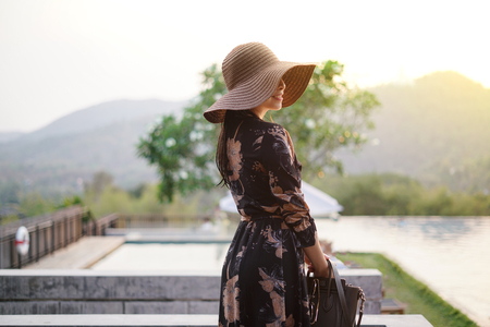 Beautiful attractive woman at the swimming terrace with oversize hat over her eyes, wearing a long dress