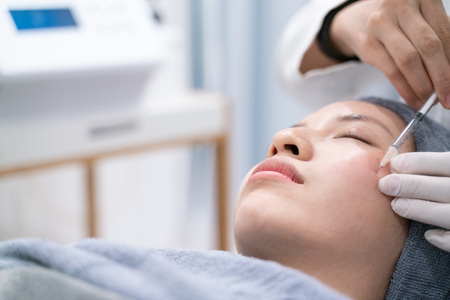 Doctors hands making an injection cosmetic in young woman face. Beauty Treatment.
