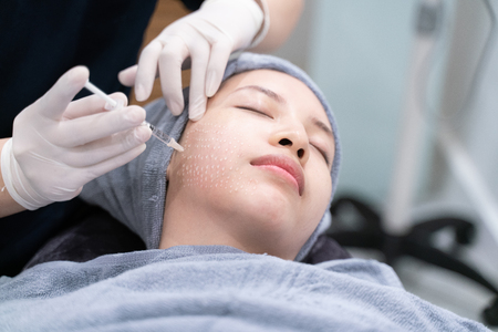 Needle mesotherapy in beauty clinic. Cosmetics injected to womans face.