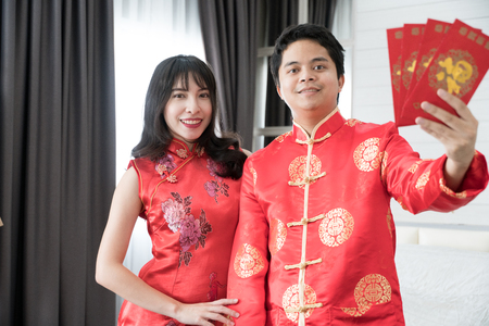 Asian man with tang suit and asian girl with cheongsam holding red envelope