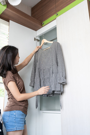 woman choosing her fashion outfit in dressing room.