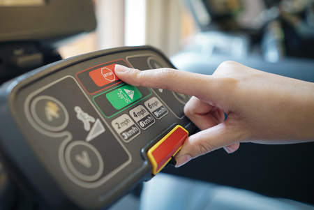 closeup of young woman athlete running on treadmill in gym. push on control panel , stop button.