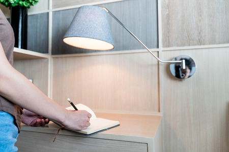 hand writing in notebook at desk with lamp 스톡 콘텐츠