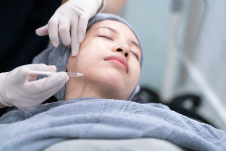 Needle mesotherapy in beauty clinic. Cosmetics injected to woman's face. 免版税图像