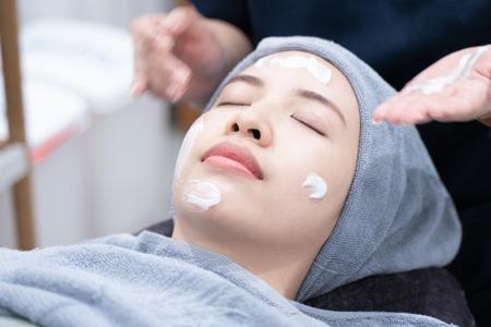 Limpieza de la piel facial mujer asiática en el salón de belleza o clínica