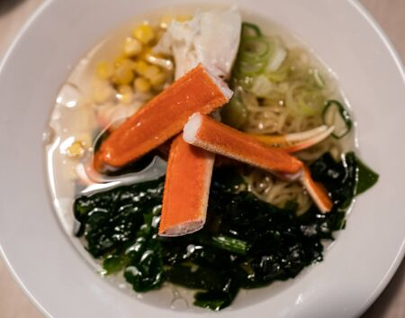 Delicious Japanese ramen noodles with Crab, and seaweed on bowl.
