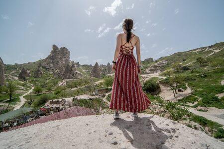 women standing from the back with Cappadocia landscape, goreme view rock mountain, TURKEY