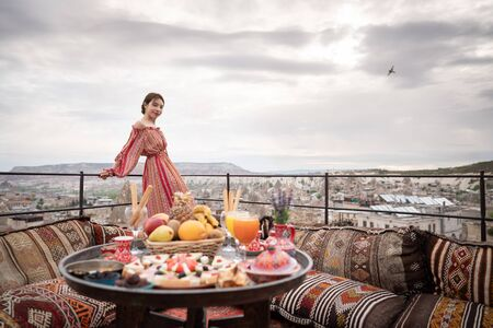 Happy women on rooftop of cave house enjoying of Goreme city panorama, Cappadocia Turkey.