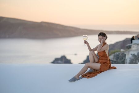 Asian woman in sexy dress witha glass of wine enjoying View Oia village in Santorini island, Greece. Stock Photo