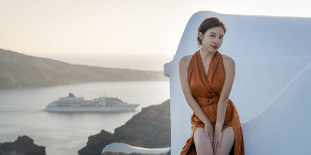 young Asian woman in sexy dress enjoying View Oia village in Santorini island, Greece. sea with the cruise ship Stock Photo