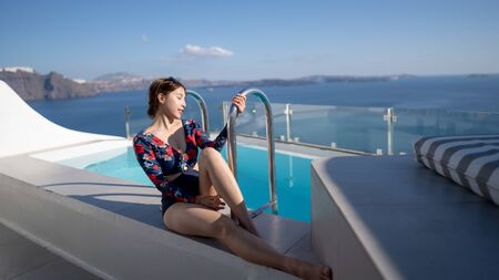 Young Asian woman in swimsuit sit near privet pool enjoying view Oia village in Santorini island, Greece.