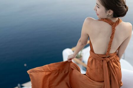 Back side of young Asian woman in sexy dress enjoying View Oia village in Santorini island, Greece.