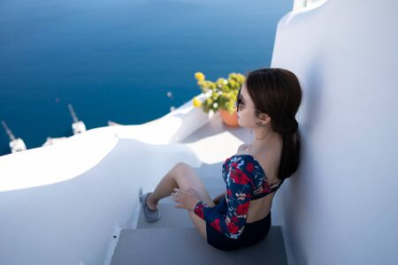 Back side of women posing on some steps at Oia village in Santorini island, Greece